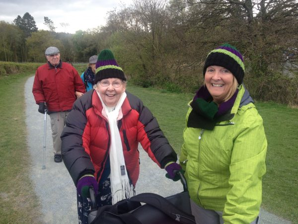 Lady with dementia walking and carer