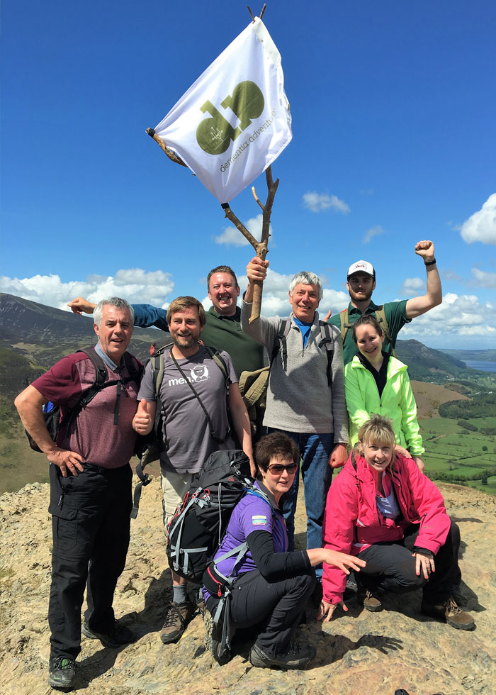 Group celebrating a climb to the top with a Dementia Adventure flag