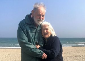 Elderly couple with dementia enjoying being on the beach