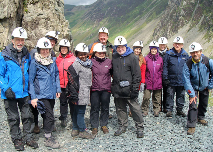 Group on a hill walk wearing safety helmets